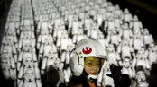 """A Chinese Star Wars fan dressed in costume poses for a photo in front of hundreds of miniature storm trooper figures placed atop the Juyongguan section of the Great Wall of China during a promotional event for the movie """"Star Wars: The Force Awakens"""" outside of Beijing, Tuesday, Oct. 20, 2015. The film, the newest installment in the long-running Star Wars saga, opens in the U.S. in December. (AP Photo/Mark Schiefelbein)"""